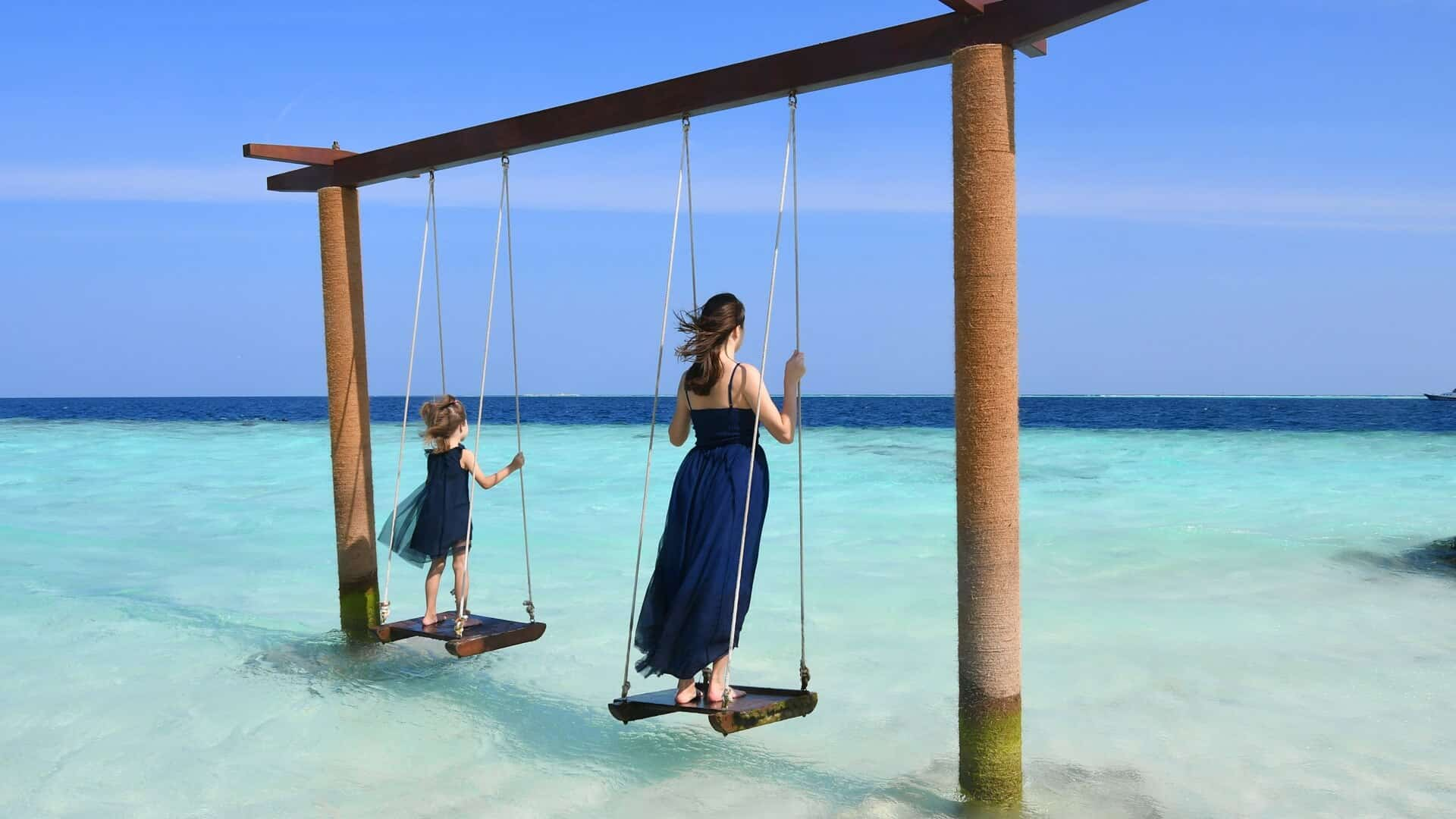 Mom and daughter on a swing in the Maldives sea